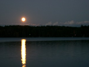 The moon rises over the lake.